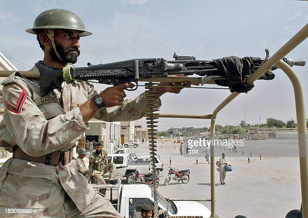 A Pakistani paramilitary soldier mans a mounted machine gun as he stands on the rear of a vehicle during a patrol in Quetta 01 September 2006...