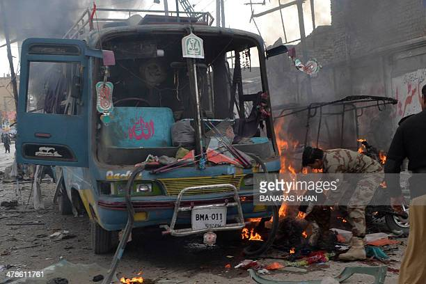 A Pakistani paramilitary soldier moves a blast victim from a mangled bus at the site of a bomb explosion in Quetta on March 14 2014 A bomb blast on...
