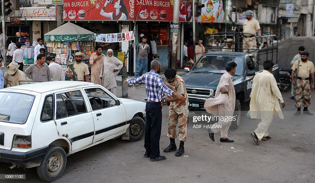 A Pakistani paramilitary soldier (C) searches a commuter on a street in Karachi on May 20, 2010. At least 17 people including two children have been killed in political clashes in Pakistan's financial capital Karachi in the past two days, a government official and police said. Police and paramilitary have been put on high alert and authorities closed all schools and colleges after the latest outbreak of politically related violence in Karachi, the biggest and richest city in Pakistan.