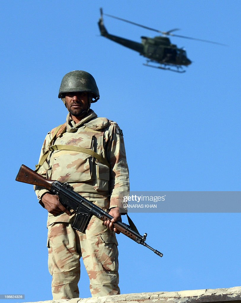 A Pakistani para-military soldier stands a top of roof a house as a security helicopter conducts surveillance during a Shiite Muslim procession in Quetta on November 22, 2012. Muslim leaders attended a rare summit in Pakistan on November 22 after militant attacks killed 36 people across the country in some of the deadliest violence claimed by the Taliban for months. Twenty-three people were killed and 62 wounded overnight in Rawalpindi, the twin city of summit venue Islamabad, where Iranian President Mahmoud Ahmadinejad and Turkish Prime Minister Recep Tayyip Erdogan were among the summit guests. AFP PHOTO/Banaras KHAN