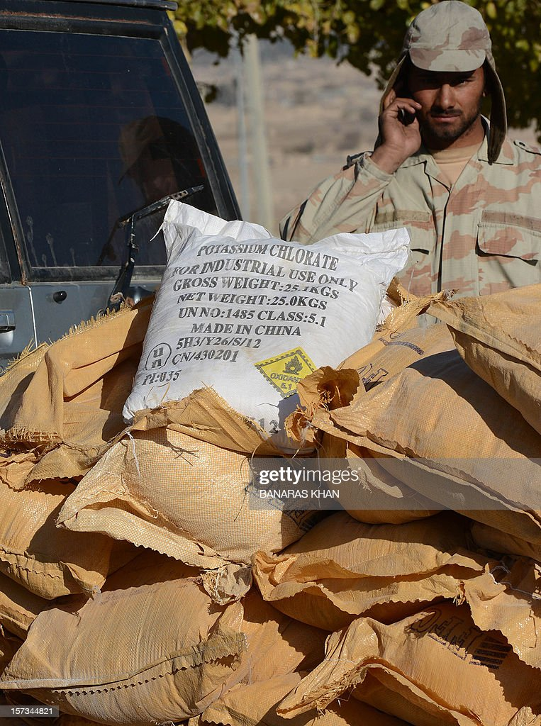 A Pakistani paramilitary soldier stands behind bags of potassium chlorate in Quetta on December 2, 2012 after police recovered tonnes of potassium chlorate from a bus. Pakistani authorities seized nearly 14 tonnes of potassium chlorate, a key ingredient in bomb-making, from a bus in the country's violent and unstable southwest on Sunday, officials said. AFP PHOTO/Banaras KHAN