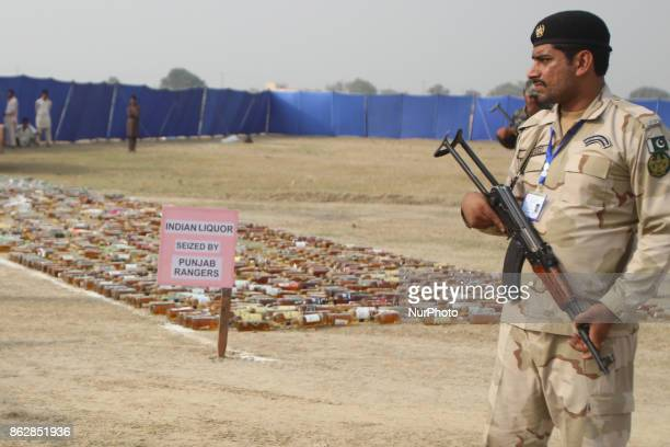 Pakistani paramilitary soldier stands gaurd as antinarcotics force seized liquor before crushing and burning the bottles Pakistani authorities...