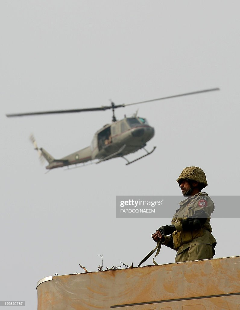 A Pakistani paramilitary soldier stands guard as a helicopter passes overhead during a religious procession on the ninth day of holy month of Moharram in Islamabad on November 24, 2012. The Pakistani Taliban have claimed responsibility for a bomb blast near a Shiite Muslim procession in northwest Pakistan that killed seven people. The blast went off as people from the minority Shiite Muslim community were gathering to mark the anniversary of the death of the Prophet Mohammed's grandson Imam Hussain in 680. AFP PHOTO/Farooq NAEEM