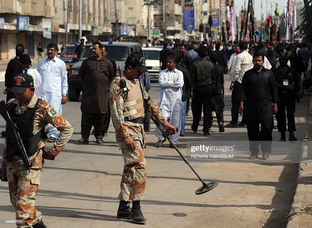 A Pakistani paramilitary soldier uses a metal detector along the roadside during a Shiite Muslim religious procession on the ninth day of holy month of Moharram in Karachi on November 24, 2012. A bomb exploded near a Shiite religious procession in northwest Pakistan on November 24 killing seven people including four children, hospital officials said. It commemorates the death of Imam Hussain, the grandson of the Prophet Mohammed, along with his close relatives and supporters in the Battle of Karbala in modern-day Iraq in the year 680. AFP PHOTO/Rizwan TABASSUM