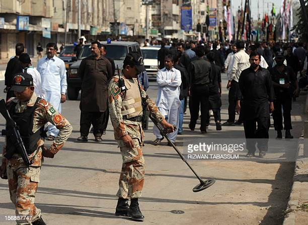 A Pakistani paramilitary soldier uses a metal detector along the roadside during a Shiite Muslim religious procession on the ninth day of holy month...