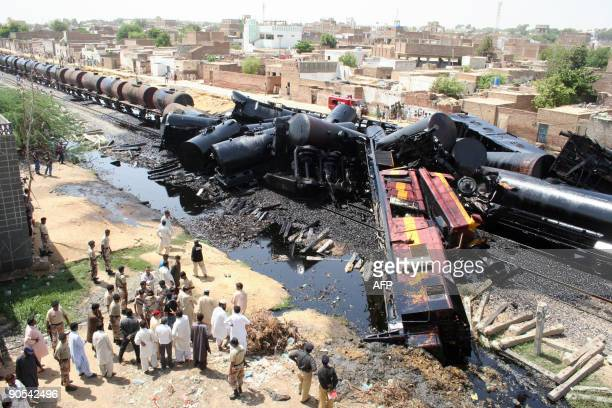 Pakistani paramilitary soldiers and officials gather beside the wreckage of oil filled wagons after the Muzaffargarhbound Oil Special derailed...
