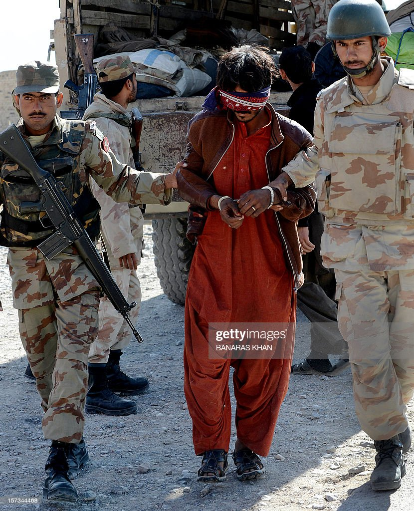 Pakistani paramilitary soldiers escort an arrested suspect into a police station in Quetta on December 2, 2012, after police recovered tonnes of potassium chlorate from a bus. Pakistani authorities seized nearly 14 tonnes of potassium chlorate, a key ingredient in bomb-making, from a bus in the country's violent and unstable southwest on Sunday, officials said. AFP PHOTO/Banaras KHAN