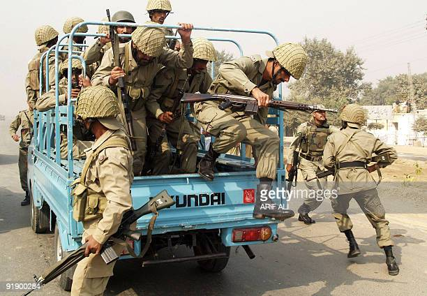Pakistani paramilitary soldiers jump from a truck as they take position outside a police training centre after gunmen attacked in Lahore on October...
