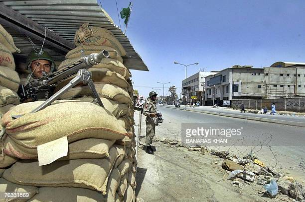 Pakistani paramilitary soldiers stand guard alongside a bunker during a strike in Quetta 26 August 2007 on the first death anniversary of...