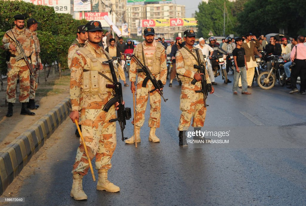 Pakistani paramilitary soldiers stand guard as activists of the ruling Pakistani Peoples Party (PPP) protest against the Supreme Court decision to arrest Pakistan Prime Minister Raja Pervez Ashraf, at a rally in Karachi on January 16, 2013. Pakistan's top judge Tuesday ordered the arrest of the prime minister over graft allegations, threatening to worsen turmoil as thousands of protesters demanded parliament be dissolved. AFP PHOTO/Rizwan TABASSUM