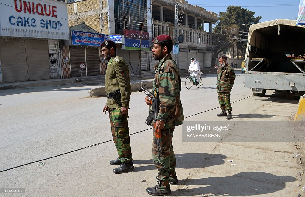 Pakistani paramilitary soldiers stand guard on a street following yesterday's bomb attack victims in Quetta on February 17, 2013. The death toll from a devastating bomb attack on Shiite Muslims in southwest Pakistan rose to 81 Sunday, as the community threatened protests if swift action was not taken against the killers. AFP PHOTO/Banaras KHAN