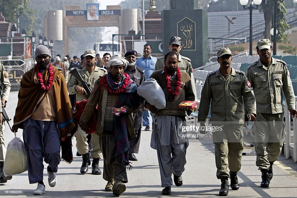 Pakistani paramilitary soldiers walk with prisoners released by the Indian government on the Wagah border on February 12, 2013. The Indian government released three prisoners of Pakistani nationality, local media reported. AFP PHOTO/ Arif ALI