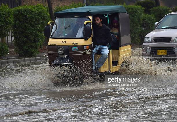 A Pakistani passenger sits in an autorickshaw while crossing a flooded street after heavy rain in Karachi on January 14 2017 / AFP / RIZWAN TABASSUM