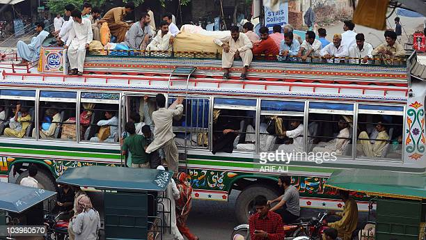 Pakistani passengers climb onto overloaded bus to return to their hometowns for the Eid alFitr festival in Lahore on September 9 2010 Bus and train...