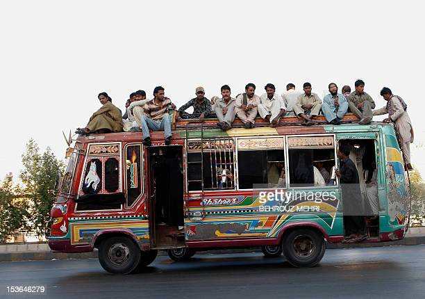 Pakistani passengers sit on the roof of a public city bus in the city of Karachi on February 20 2010 AFP PHOTO/BEHROUZ MEHRI