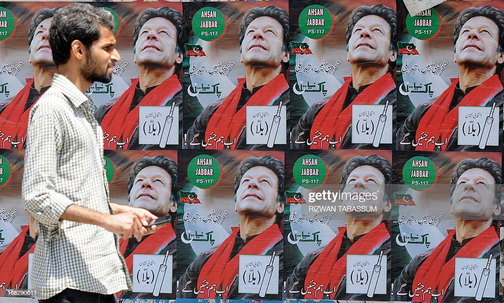 A Pakistani pedestrian walks past electoral posters of Pakistani politician and former cricketer Imran Khan, in Karachi May 8, 2013. Pakistani politician Imran Khan has been advised to rest for a week after sustaining skull and back injuries in a fall at an election campaign rally, a hospital official said. The former cricket star was admitted to the private Shaukat Khanum hospital that he founded in Lahore on May 7 after falling off a lift taking him to the stage at a rally ahead of Pakistan's general election on Saturday. AFP PHOTO / RIZWAN TABASSUM