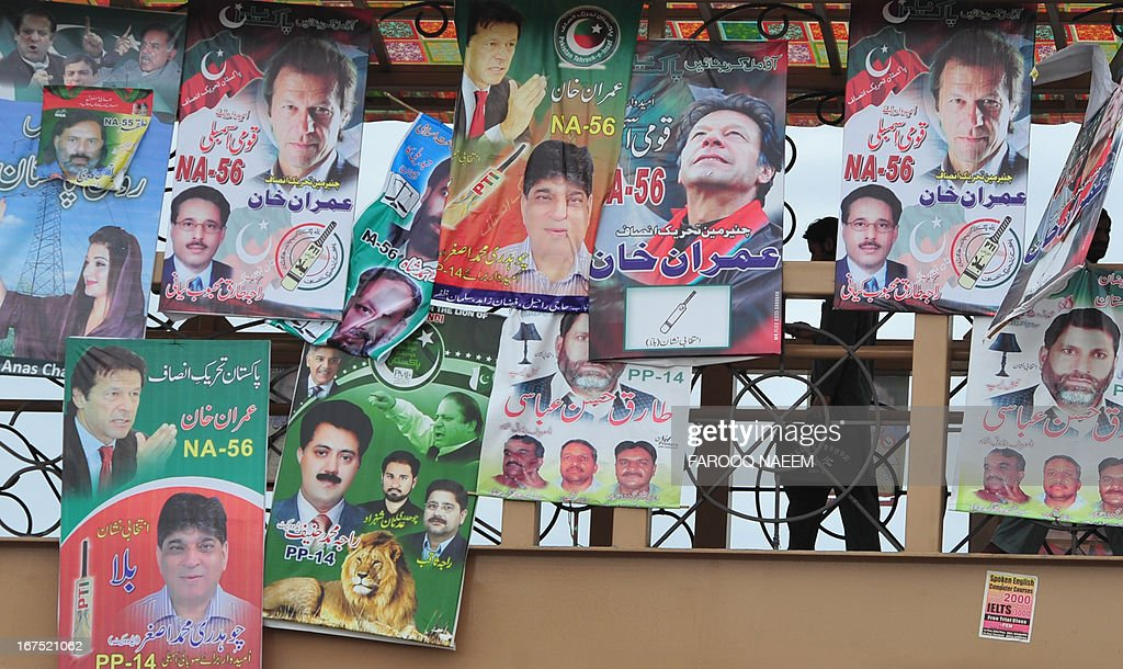 A Pakistani pedestrian walks past electoral posters on a bridge in Rawalpindi on April 26, 2013. May 11 national polls should see power pass from a civilian government that has served a full term to another through the ballot box for the first time in the nuclear-armed country's turbulent history. AFP PHOTO/Farooq NAEEM