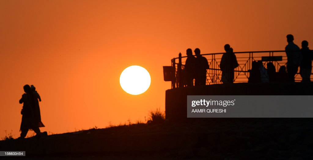 Pakistani pedestrians look at the last sunset of 2012 at a lake view point in Islamabad on December 31, 2012. Sydney will kick off a wave of dazzling firework displays welcoming in 2013, from Dubai to Moscow and London, with long-isolated Yangon joining the global pyrotechnics for the first time. AFP PHOTO/ Aamir QURESHI
