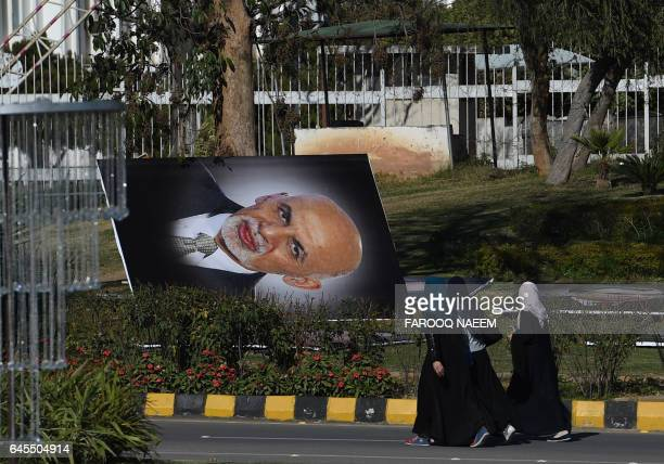 TOPSHOT Pakistani pedestrians walk past a portrait of Afghan President Ashraf Ghani before it is installed on a street in Islamabad on February 26...