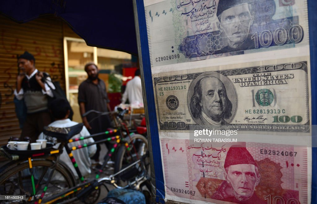 Pakistani pedestrians walk past a roadside currency exchange stall displaying examples of Pakistani and US currency notes in Karachi on February 11, 2013. The Pakistani rupee on February 11 sank to an all-time low against the US dollar over forex reserve fears as the country repayed $146 million to the International Monetary Fund. AFP PHOTO/Rizwan TABASSUM
