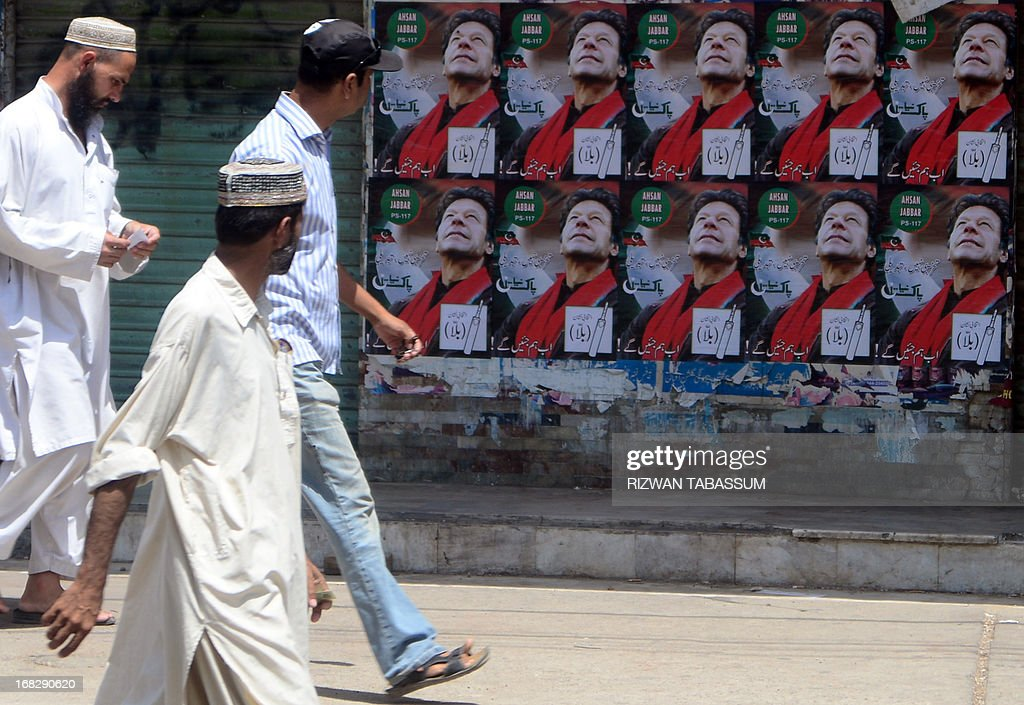 Pakistani pedestrians walk past electoral posters of Pakistani politician and former cricketer Imran Khan, in Karachi May 8, 2013. Pakistani politician Imran Khan has been advised to rest for a week after sustaining skull and back injuries in a fall at an election campaign rally, a hospital official said. The former cricket star was admitted to the private Shaukat Khanum hospital that he founded in Lahore on May 7 after falling off a lift taking him to the stage at a rally ahead of Pakistan's general election on Saturday.
