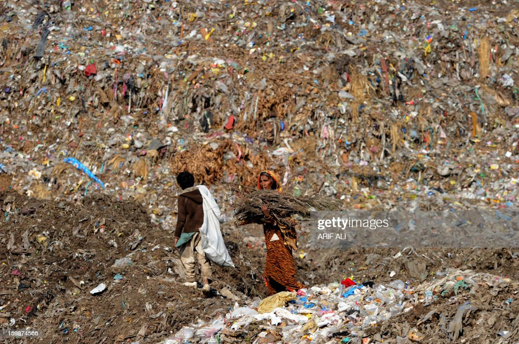 Pakistani people collect recyclable items at a landfill site in Lahore on January 22, 2013. AFP PHOTO/Arif ALI