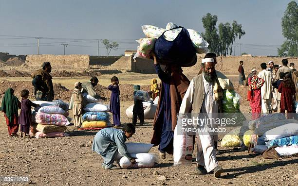 Pakistani people from the Tribal areas made homeless by the ongoing conflict walk away after receiving relief goods at the Jalozai camp some 40kms...