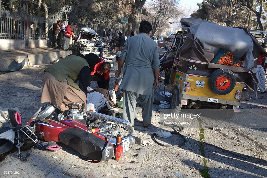 Pakistani people gather around a body a victim at the site of a suicide attack in Quetta, Pakistan, on February 6, 2016. At least nince people were killed and several others wounded in the suicide attack near the premises of the heavily guarded Quetta district courts on Saturday.