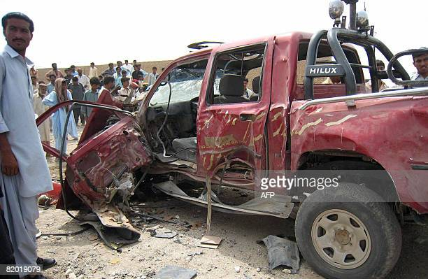 Pakistani people gather around a damaged vehicle hit by a road side blast at Dera Bugti district in southwestern Baluchistan province on July 21 2008...
