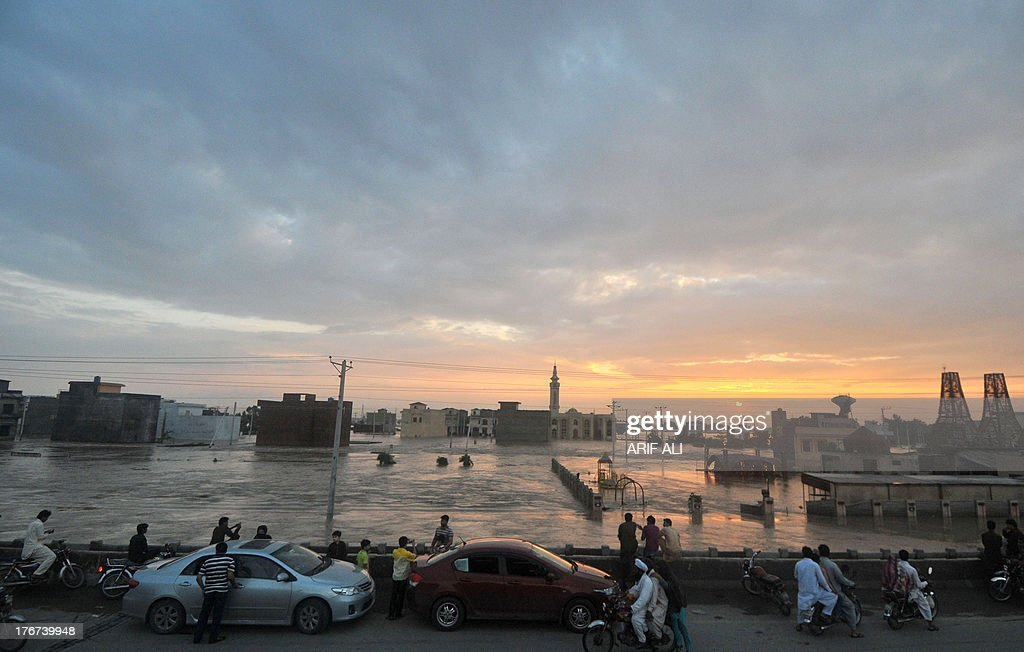Pakistani people look at flood waters at Kala Shah Kako on August 18, 2013. Heavy monsoon rains have triggered floods affecting more than 300,000 people across Pakistan in the last two weeks and killed 108 others, disaster management officials said. AFP PHOTO/Arif ALI
