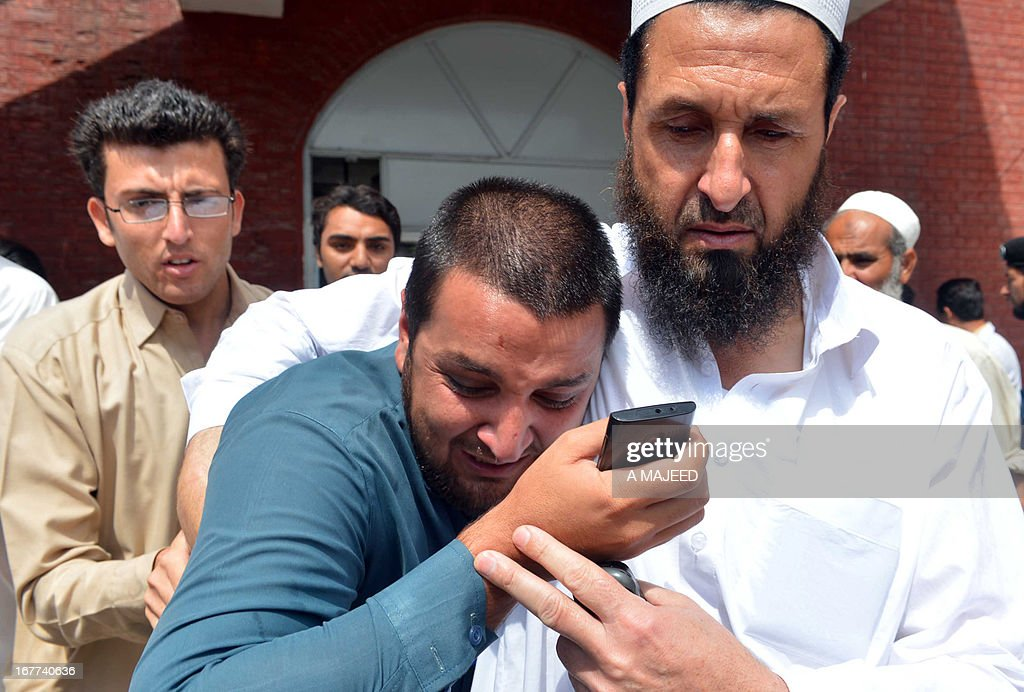 Pakistani people mourn the death of a relative in a bomb blast in Peshawar on April 29, 2013. A suicide bomber killed at least eight people and wounded 45 others when he rammed his motorcycle into a bus in Pakistan's northwestern city of Peshawar on Monday, police said.