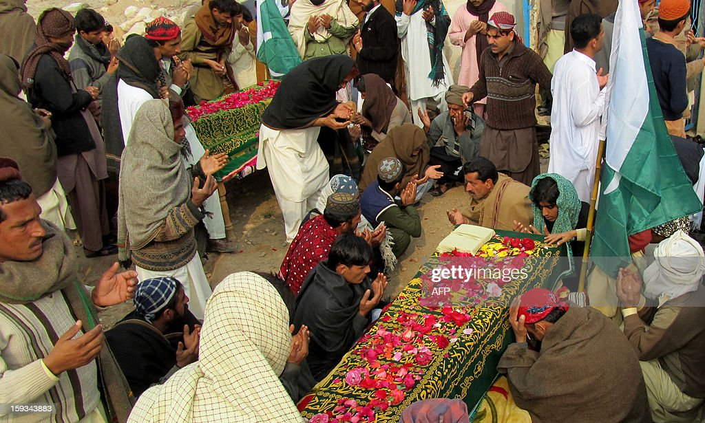 Pakistani people offer prayers at the coffins of Frontier Constables (FC) who were killed in twin bombings in Quetta, during the funeral ceremony in Mianwali on January 12, 2013. FC personnel were among 92 people who died in one of the deadliest terror attacks in the country's southwestern Quetta city. AFP PHOTO/Ghulam AKBAR
