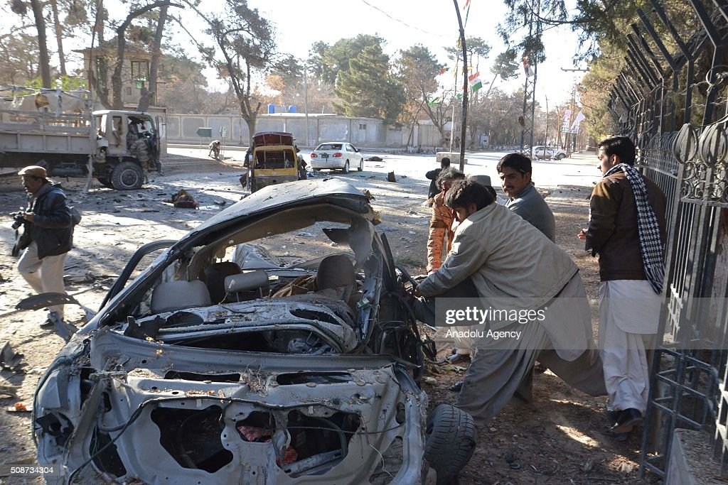Pakistani people pull out a body from a destroyed vehicle at the site of a suicide attack in Quetta, Pakistan, on February 6, 2016. At least nince people were killed and several others wounded in the suicide attack near the premises of the heavily guarded Quetta district courts on Saturday.