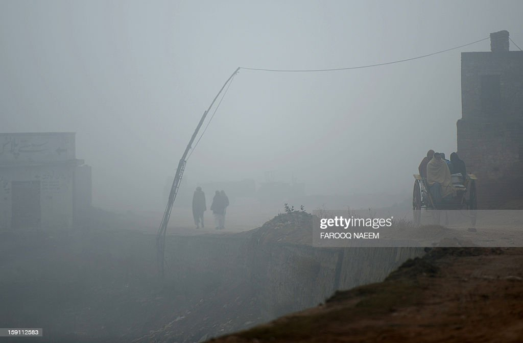 Pakistani people travel along the road during a foggy morning in Islamabad on January 8, 2012. The fog has also disrupted flight schedules at the Islamabad airport and four Islamabad-bound flights from Dubai and Afghanistan were diverted to Lahore. AFP PHOTO/Farooq NAEEM