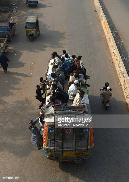Pakistani people travel on a bus during a strike called following the deadly bomb attack at a Shiite Mosque in Shikarpur district in Karachi on...