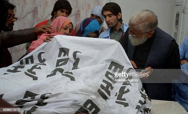 Pakistani people try to identify the body of a polio health worker at a hospital in Quetta Pakistan on November 26 2014 Four polio workers including...