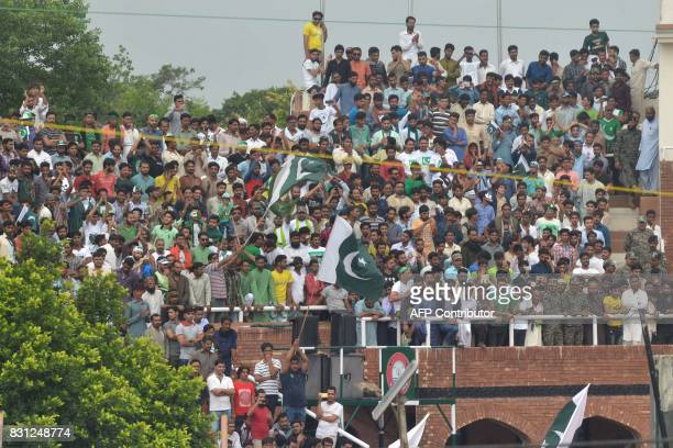 Pakistani people wave the Pakistani flags during a ceremony to celebrate Pakistan's Independence Day at the IndiaPakistan Wagah border post on August...