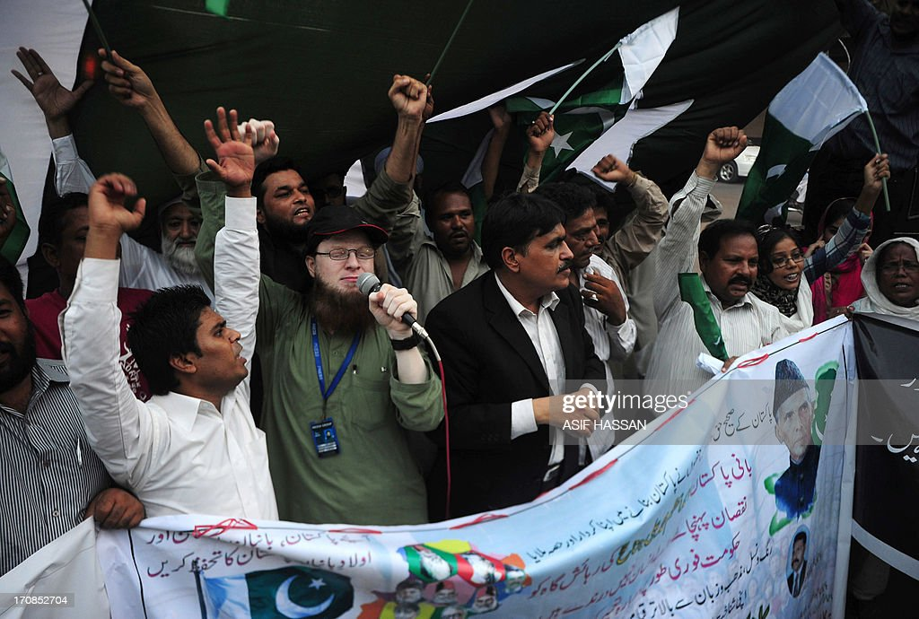 Pakistani peoples hold national flags as they shout slogans during a rally in Karachi on June 19, 2013, to protest for the bombing in Quetta and against militants who destroyed a historic building linked to Pakistan's founding father Mohammad Ali Jinnah. At least 25 people were killed June 15 when militants blew up a bus carrying female students in Quetta, capital of restive Baluchistan province, and then stormed a hospital where survivors had been taken for treatment. AFP PHOTO/Asif HASSAN