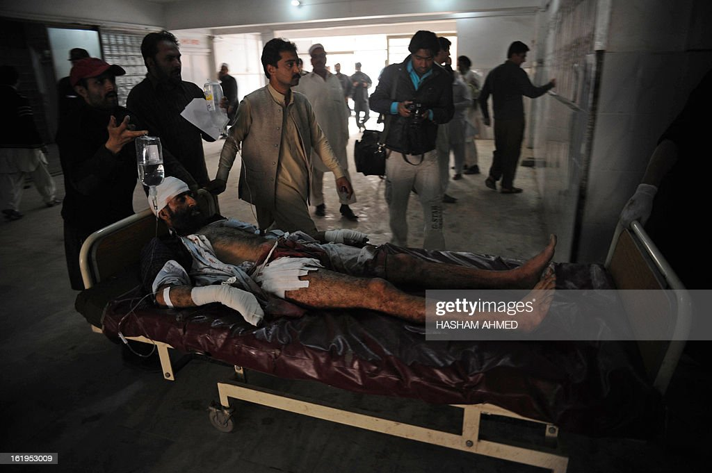 Pakistani peoples shift an injured victim into the hospital after the militants' attack on the office of the top political official of Khyber tribal region in Peshawar on February 18, 2013. Militants including a suicide bomber attacked the office of a senior official in Pakistan's northwestern city of Peshawar on Monday, killing five people, officials said. AFP HOTO/Hasham AHMED