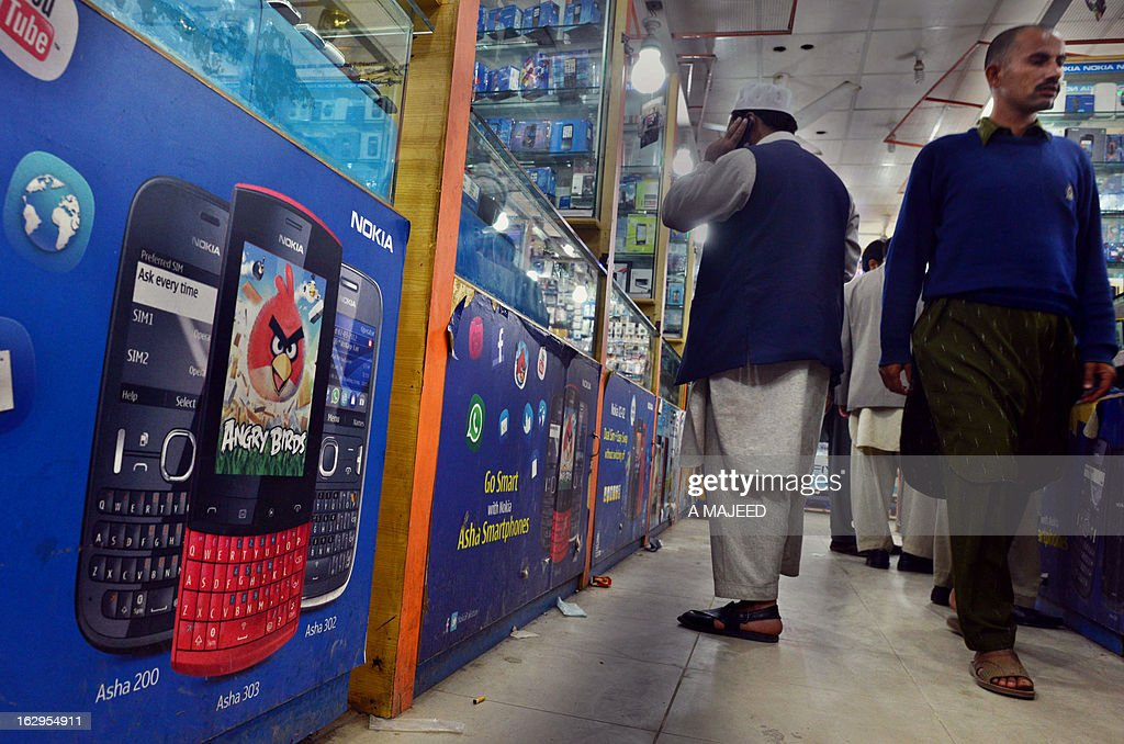 Pakistani peoples walk in a mobile market in Peshawar on March 2, 2013. Pakistani Taliban have threatened to bomb a mobile phone market in the northwestern city of Peshawar for the 'shameless' selling of video clips, ring tones and accessories, officials said. AFP PHOTO/A MAJEED