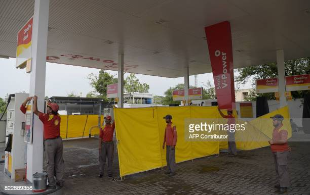 Pakistani petrol station employees cordon off the station forecourt following fuel shortages amid a countrywide strike by the All Pakistan Oil...