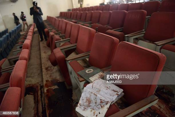 A Pakistani photographer takes photographs of a bloodied ceremony hall at an armyrun school a day after an attack by Taliban militants in Peshawar on...