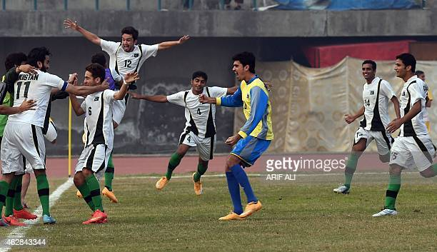 Pakistani players celebrate after score a goal against Afghanistan during their friendly football match at the Punjab stadium in Lahore on February 6...