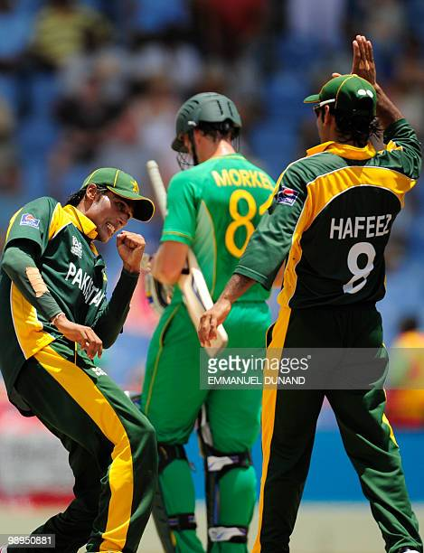 Pakistani players Mohammad Aamer and Mohammad Hafeez celebrate at the end of the ICC World Twenty20 Super Eight match between Pakistan and South...