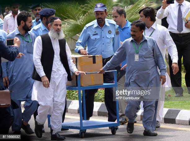 Pakistani police and court officials transport a box of final evidence presented by the Joint Investigation Team at the Supreme Court as part of the...