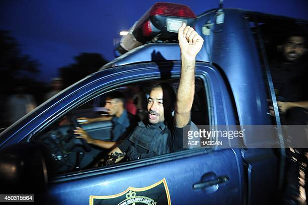 A Pakistani police commando shout slogans on his return from an operation against militants at Jinnah International Airport in Karachi on June 9 2014...