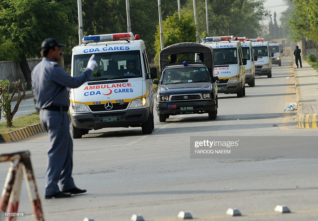 Pakistani police escort ambulances carrying the coffins of foreign tourists as they come out from Chaklala air base in Rawalpindi on June 23, 2013. Gunmen dressed as police killed nine Chinese and Ukrainian tourists in an unprecedented attack in the Pakistani Himalayas claimed by the Taliban, who said they had set up a new faction to target foreigners in revenge for US drone strikes. AFP PHOTO/ Farooq NAEEM