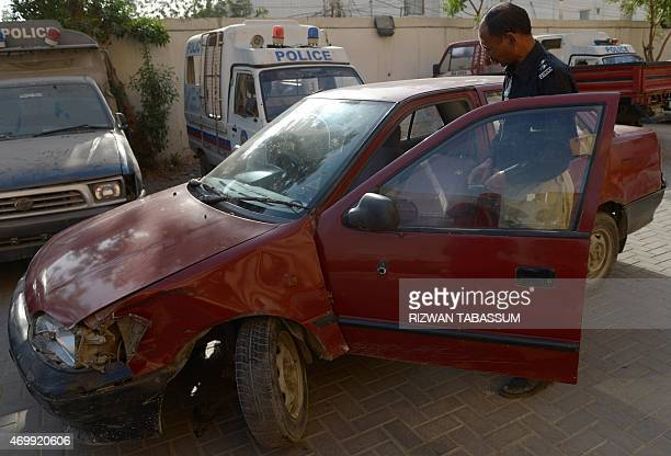 A Pakistani police officer inspects a vehicle inwhich a woman identified as a US national was shot in Karachi on April 16 2015 A woman identified by...