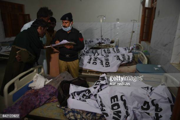 A Pakistani police officer speaks with relatives beside the covered bodies of blast victims at a local hospital in the town of Sehwan a day after a...
