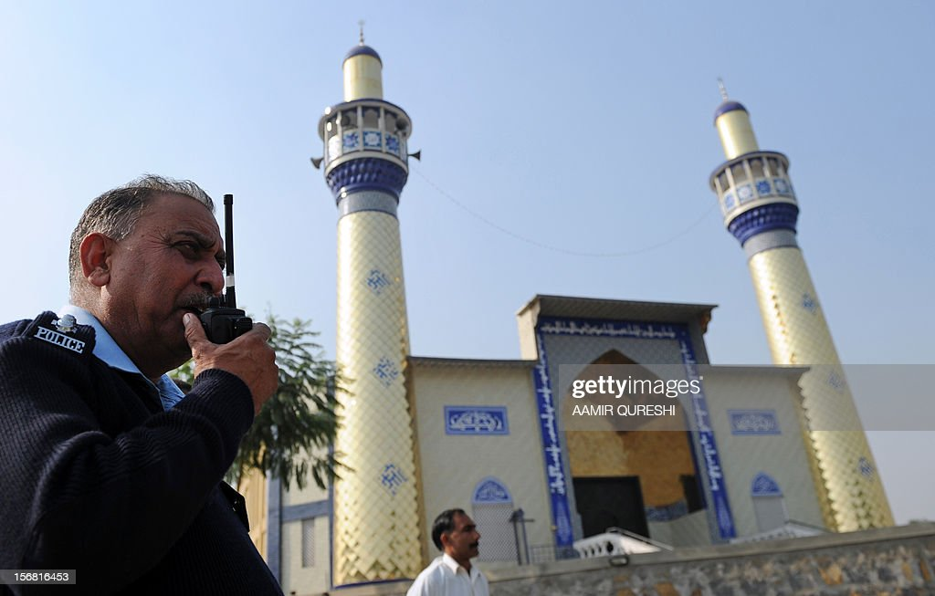 A Pakistani police officer talks over his handset as he stands guard near a Shiite Muslim mosque following overnight suicide bomb attacks on minority Shiite Muslims, in Islamabad on November 22, 2012. Muslim leaders gathered for a rare summit in Islamabad on November 22 as militant attacks killed 35 people across the country on one of the deadliest days of violence claimed by the Taliban in months. Twenty-three people were killed and 62 wounded overnight in Rawalpindi, the twin city of Islamabad, where Iranian President Mahmoud Ahmadinejad and Turkish Prime Minister Recep Tayyip Erdogan are chief among the summit guests. AFP PHOTO/Aamir QURESHI